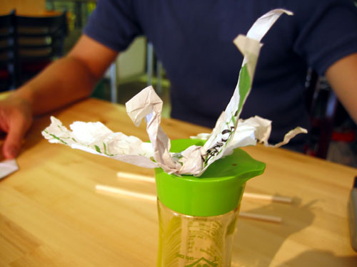 A bird made out of chopstick wrapers.