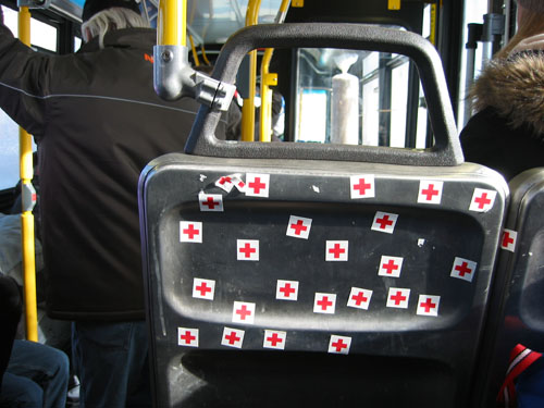 Red Cross stickers on the back of a bus seat.