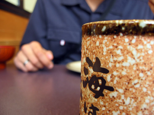 A cup of green tea in the foreground, Rishi in the background.