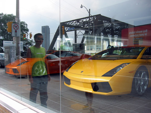 Two lamborghinis in a show room window.  A reflection of Simon in the glass.