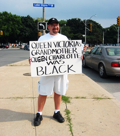 A man holding a sign outside of the CNE.