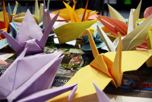 A few paper cranes on a table.