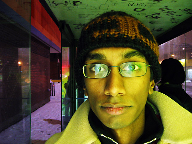A picture of me standing in a bus shelter late at night.