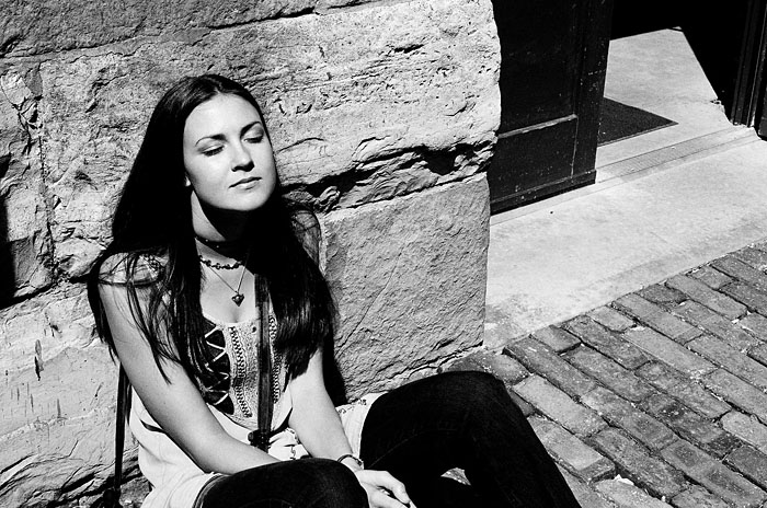 Caroline resting against a wall in the distillery district.