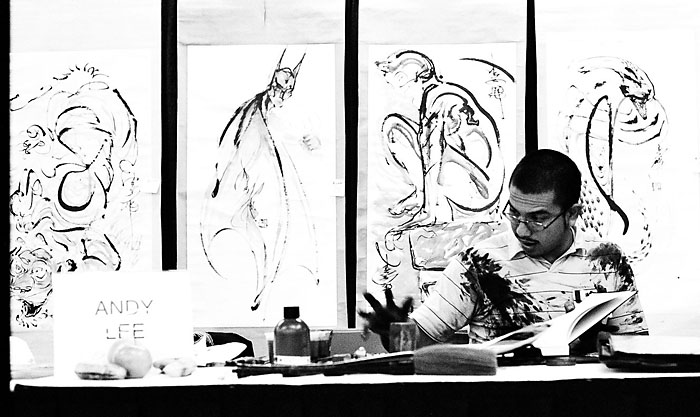 Andy Lee sitting in front of some of his artwork.